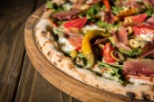 Fotografie close up view of freshly baked italian pizza on wooden cutting board