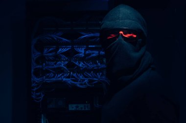 obscured view of hacker in eyeglasses and mask looking at camera with cables on background