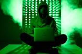 Fotografie getönten Bild von Hacker in Hoodie mit Laptop und Dreieck