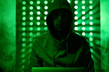 Toned picture of male hacker in hoodie with laptop stock vector