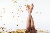 oříznutý obraz žena na lůžku s nohama pod padající konfety na bílém