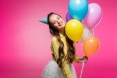 atraktivní žena pózuje s karnevalovou čepičku a balónky izolovaných na růžové