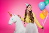 krásná dívka s party hat, balónky a jednorožec hračka izolované na růžové
