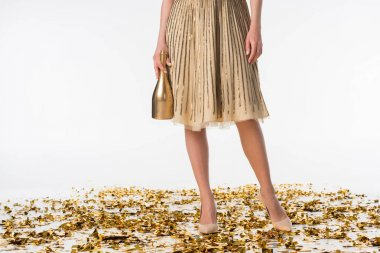 cropped image of girl standing on confetti in skirt and holding bottle of champagne