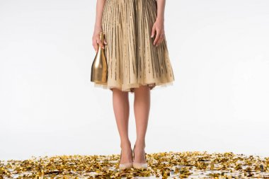 cropped image of woman standing on confetti in skirt and holding bottle of champagne