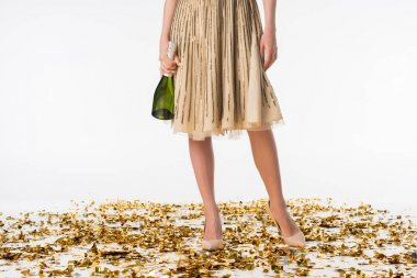 cropped image of girl standing on confetti and holding bottle of champagne