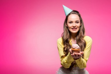 attractive woman with party hat holding cupcake with candle isolated on pink