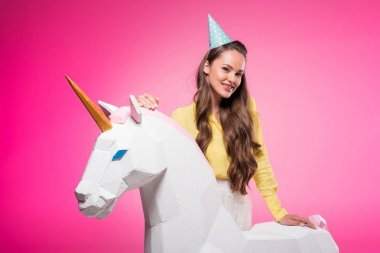attractive woman with party hat ant unicorn toy isolated on pink