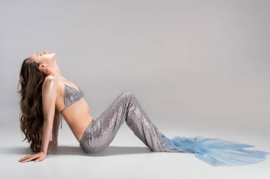 side view of beautiful woman with mermaid tail lying on floor