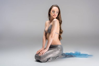 attractive woman with mermaid tail and silver top sitting on floor