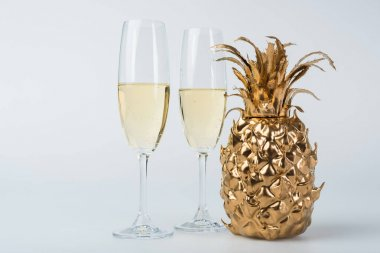Glasses of champagne and golden pineapple on white stock vector
