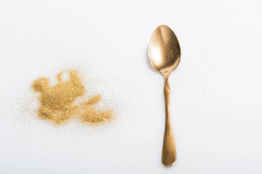 golden spoon and bright glitter isolated on white