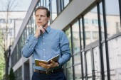 thoughtful businessman with diary and pen standing near office building