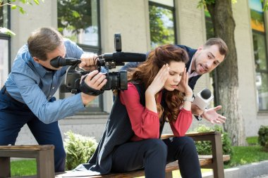 cameraman and news reporter talking to stressed businesswoman
