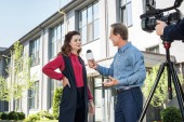 Photo cameraman and male news reporter interviewing successful businesswoman