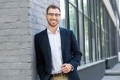 Fotografie cheerful professional businessman posing near office building