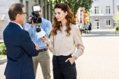 Photo cameraman with digital video camera and female journalist interviewing professional businessman