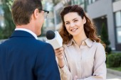 smiling anchorwoman with microphone interviewing professional businessman