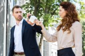 Fotografie angry businessman refusing interview, female journalist holding microphone