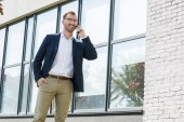 Photo smiling businessman in formal wear talking on smartphone near office building