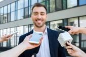 Fényképek interjúk sikeres üzletember, a mikrofonok és okostelefonok mosolyogva újságírók
