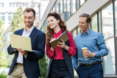 smiling business team with disposable cup of coffee working together with laptop and diary