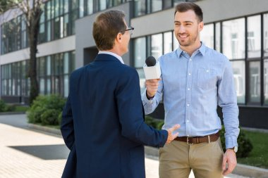 professional smiling journalist interviewing successful mature businessman with microphone