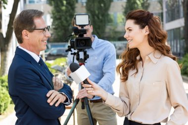 cameraman and female news reporter with microphone interviewing professional businessman