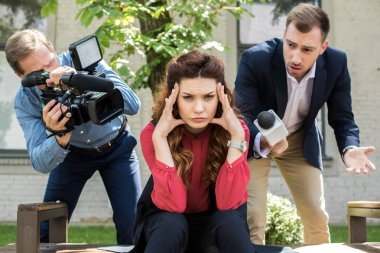 cameraman with digital video camera and male newscaster with microphone talking to tired businesswoman