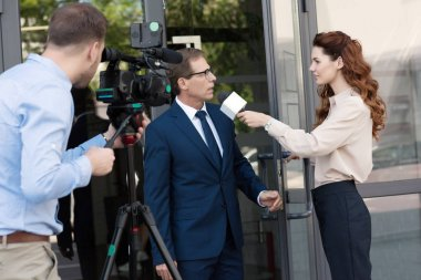 cameraman with digital video camera and professional anchorwoman interviewing businessman near office building