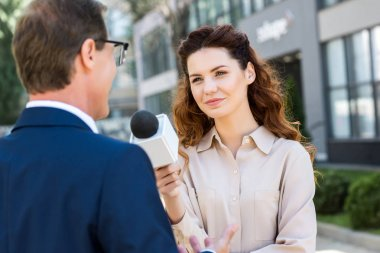 beautiful journalist with microphone interviewing professional businessman