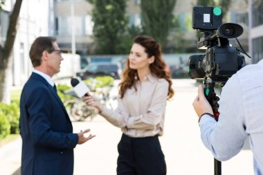 cameraman and anchorwoman with microphone interviewing businessman