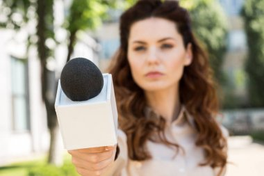 selective focus of serious anchorwoman taking interview with microphone