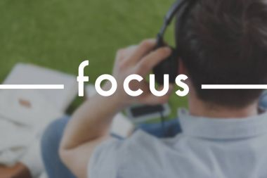 close-up shot of man in headphones sitting on grass, focus inscription