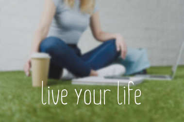cropped shot of woman sitting on grass with cup of coffee to go and working with laptop, live your life inscription