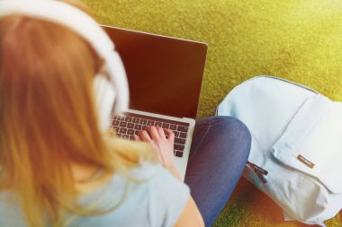 high angle view of young woman sitting on grass with headphones on head and working with laptop