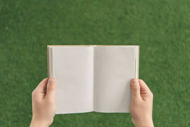 Cropped shot of man holding blank book against green grass stock vector