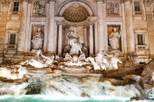 Trevi Fountain with ancient sculptures near water in rome