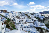 white houses on hill against sky with clouds in greece
