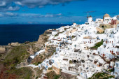 white houses near tranquil sea against sky with clouds in santorini