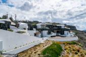 bílé domy v blízkosti zelených rostlin proti obloze s mraky
