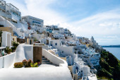 SANTORINI, GREECE - APRIL 10, 2020: white houses near tranquil aegean sea against sky with clouds