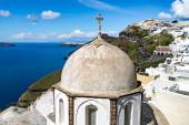 sunlight on church near white houses and tranquil aegean sea in Santorini island