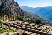 sunshine on ancient columns near tranquil mountains in greece