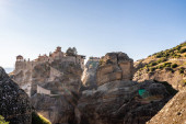 sluneční svit na ortodoxní klášter na skalních útvarech proti modré obloze v meteoře