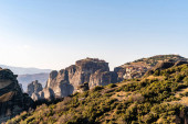 rock formations with monastery near mountains in meteora