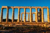 slunce na prastarých sloupcích parthenonu v Aténách proti modré obloze