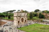 ŘÍM, ITÁLIE - 10. dubna 2020: lidé kráčející v blízkosti starobylého oblouku titusu v Římě