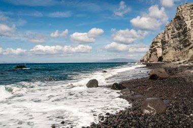 blue aegean sea near rocks against sky with clouds