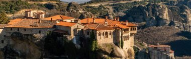 panoramic shot of monastery of holy trinity on rock formations in meteora